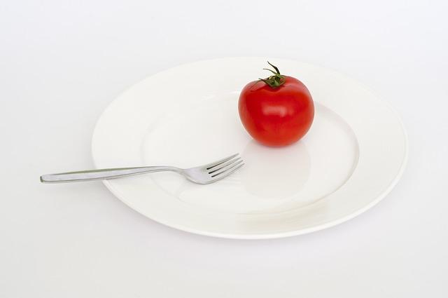 prázdný talíř, rajče a vidlička